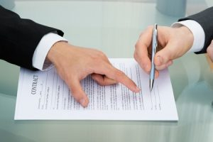 person pointing on paper to sign on contract, entrust payroll service, florida - iamge